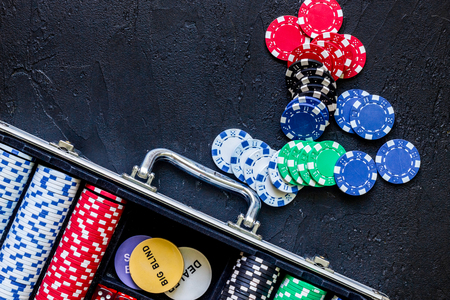 Poker set in a metallic case on a grey table top view copyspace
