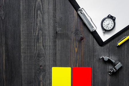 Amarillo y rojo tarjetas de árbitro y silbato sobre fondo de madera vista superior. Foto de archivo