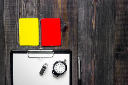 Yellow and red referee cards and whistle on wooden background top view. Stock Photo