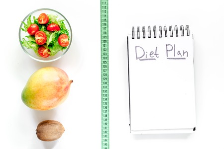 Tasty food for slimming. Notebook for diet plan, salad, fruits and measuring tape on white background top view mock up Stock Photo