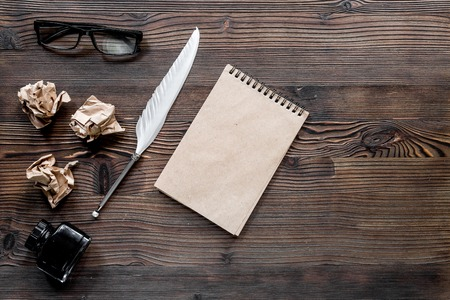 Writer concept. Feather pen, vintage notebook and crumpled paper on wooden table background top view.
