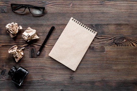 Writer concept. Feather pen, vintage notebook and crumpled paper on wooden table background top view. Stock Photo - 81413421