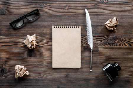 Writer concept. Feather pen, vintage notebook and crumpled paper on wooden table background top view. Stock Photo - 81413422