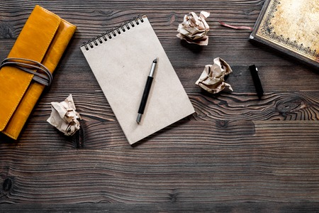Writer concept. Pen, vintage notebook and crumpled paper on wooden table background top view.