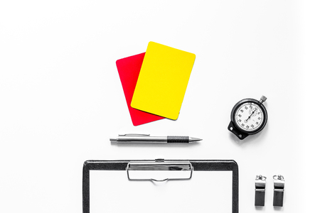 Set to judge competition. Yellow and red cards, stopwatch, whistle, pad on wooden background top view.
