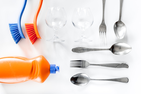 Wash dishes. Tableware, liquid and brushes on white background top view Stock Photo