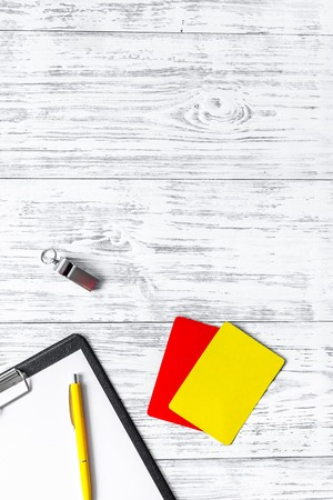 Referee tools. Yellow and red cards, whistle, pad on wooden background top view copyspace.