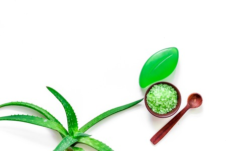 Skin care. Aloe vera leafs and spa salt on wooden background top view. Stock Photo