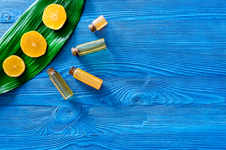 Skin care. Citrus oil and lotion on blue wooden background top view. Reklamní fotografie