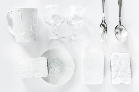 Sponge and tableware on white background top view. Stock Photo