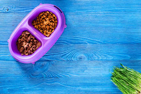 Animal feed in bowl and grass on blue table background top view.