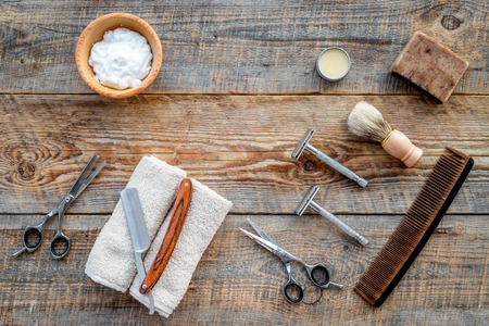 Barbershop. Mens shaving and haircut. Brush, razor, foam, sciccors on wooden table background top view.
