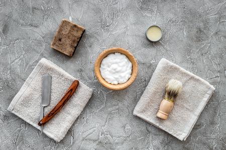 Preparing for men shaving. Shaving brush and razor on grey stone table background top view.