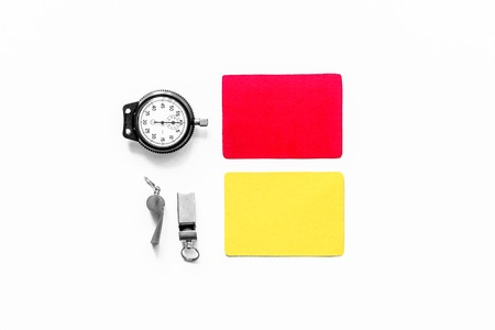 Referee tools. Yellow and red cards, stopwatch, whistle on white background top view copyspace.