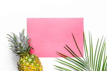 Pineapples and palm branch on white background top view. Zdjęcie Seryjne