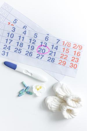 Zwangerschap planning. Zwangerschapstest, kalender en buiten op witte hoogste mening als achtergrond.