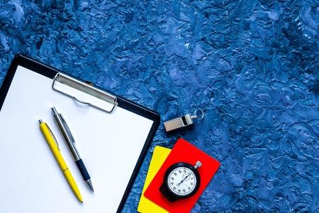 Set om competitie te beoordelen. Gele en rode kaarten, stopwatch, fluitje, pad, pen op blauwe tafel achtergrond bovenaanzicht.