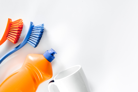 Dishwashing liquid, brushes and tableware on white background top view. Stock Photo