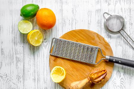Preparing lemonade. Lemon, lime, grater on wooden background top view
