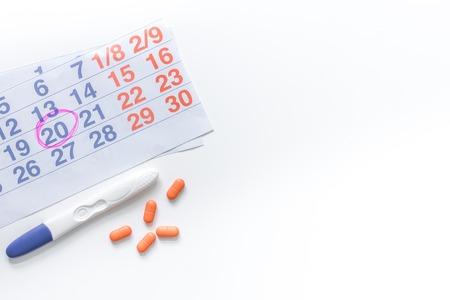 Pregnancy planning. Pregnancy test, calendar and pills on white background top view copyspace. Zdjęcie Seryjne