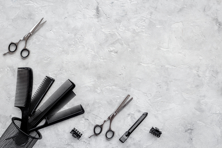 Combs and hairdresser tools on grey table background top view.