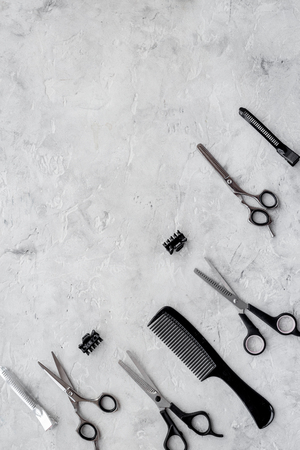 Hairdresser workplace. Combs and sciccors on grey table background top view.