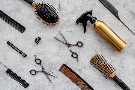 Pattern of combs and hairdresser tools on grey table background top view.