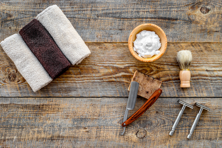 Barbershop. Mens shaving and haircut. Brush, razor, foam on wooden table background top view.