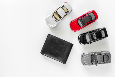 Buying car. Toy cars and wallet on white background top view.