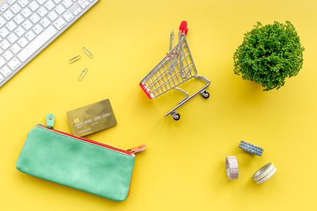 Online shopping. Bank card in purse nearby keyboard and mini shopping cart on yellow background top view. Stock Photo