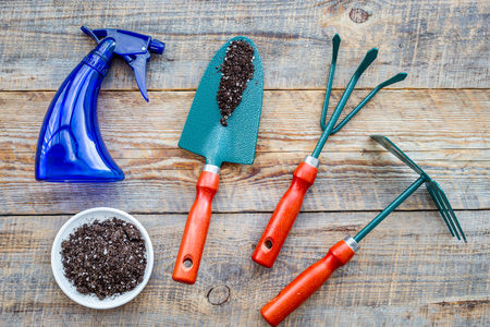 Working in garden. Gardening tools and pots with soil on wooden background top view 版權商用圖片