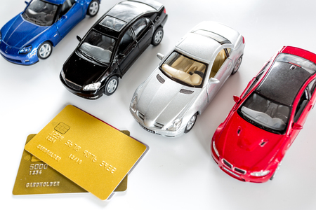 Choosing car concept. Toy cars and bank card on white background top view Stock Photo