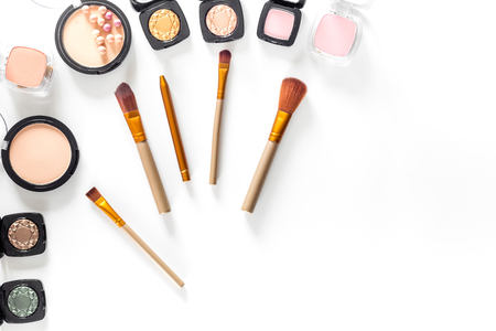 Makeup kit. Eyeshadows, brushes, blushes on white table background top view copyspace Фото со стока