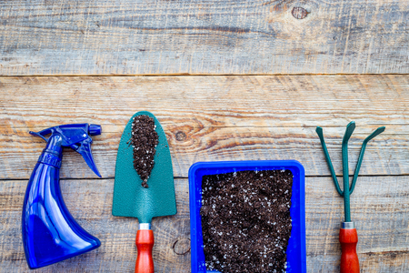 Working in garden. Gardening tools and pots with soil on wooden background top view copyspace Stock Photo