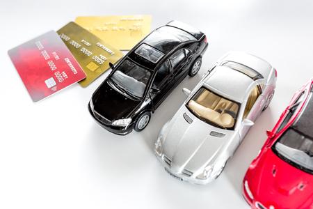 Het kiezen van auto-concept. Stuk speelgoed auto's en betaalpas op witte hoogste mening als achtergrond copyspace. Stockfoto