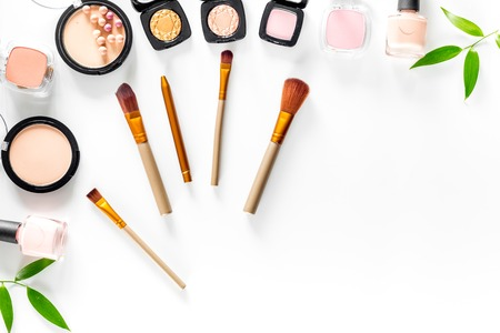 Makeup kit. Eyeshadows, brushes, blushes on white table background top view. Фото со стока