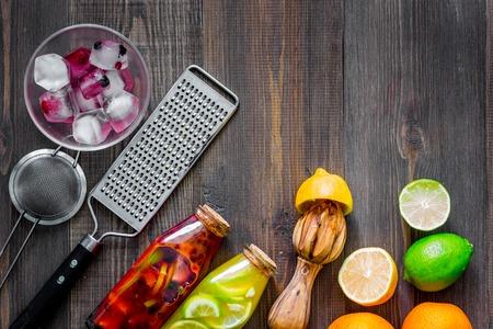 Limonade maken. Cookware, vruchten, fles limonade op houten lijst hoogste mening als achtergrond copyspace Stockfoto