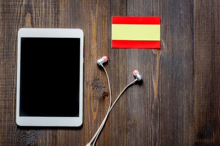 Self-development. Learning spanish online. Headphones and tablet PC on wooden background top view copyspace mockup 版權商用圖片