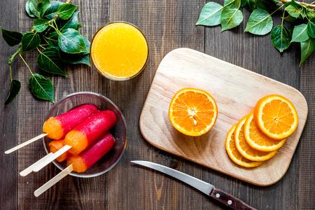 Oranges, orange juice and citrus ice cream on wooden table background top view