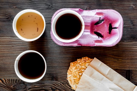 Coffee take out. Coffee cups with covers and cookies on wooden table backound top view.