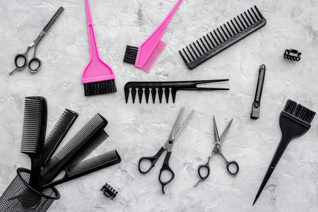 hair stylist: Combs and hairdresser tools on grey table background top view.
