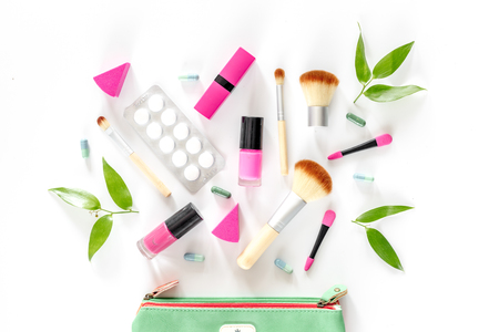 Contents of wonams beauty bag. Cosmetics, contraceptives and pills on white background top view.