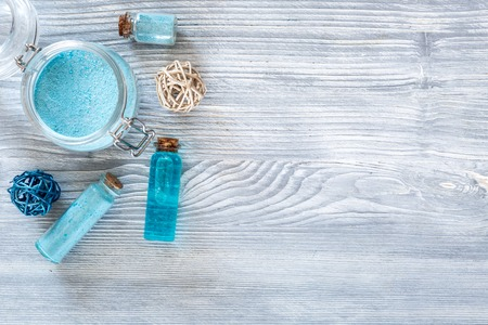 Spa set with sea salt, blue clay and lotion on blue wooden table background top view.
