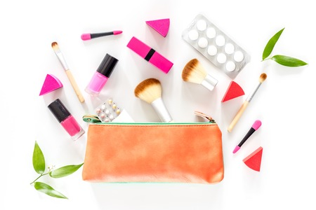 Beauty bag with cosmetics, contraceptives and pills on white table background top view. Stock Photo