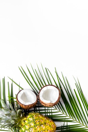 Concept of summer tropical fruits. Pineapple and palm branch on white background top view.