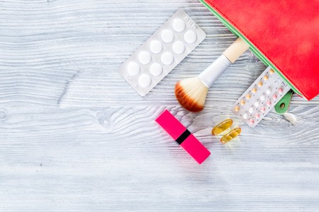 Contents of wonams beauty bag. Cosmetics, contraceptives and pills on wooden table background top view. Фото со стока