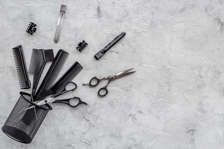 hair stylist: Hairdresser workplace. Combs and sciccors on grey table background top view.