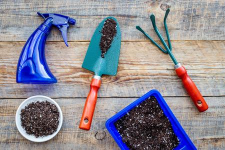 Werken in de tuin. Het tuinieren hulpmiddelen en potten met grond op houten hoogste mening als achtergrond