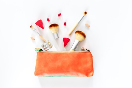 Beauty bag with cosmetics, contraceptives and pills on white table background top view. Фото со стока