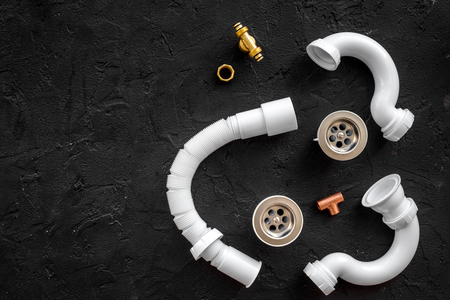 Disassembled sink drain pipe on black stone background top view.